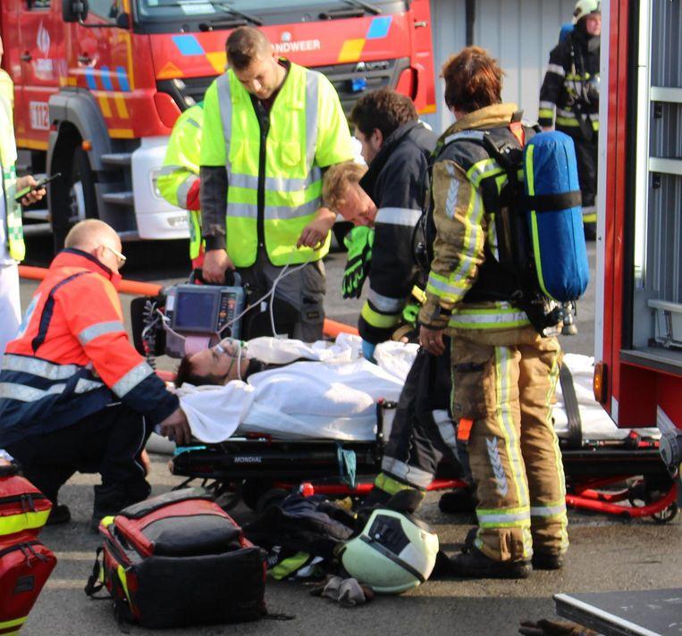 De brandweerman krijgt zuurstof op de draagberrie.