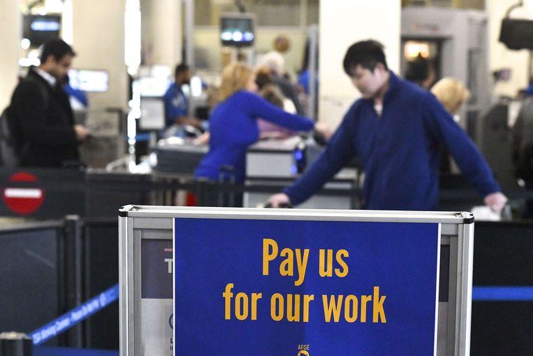 'Betaal ons voor ons werk' staat op een bord in Philadelphia Airport.