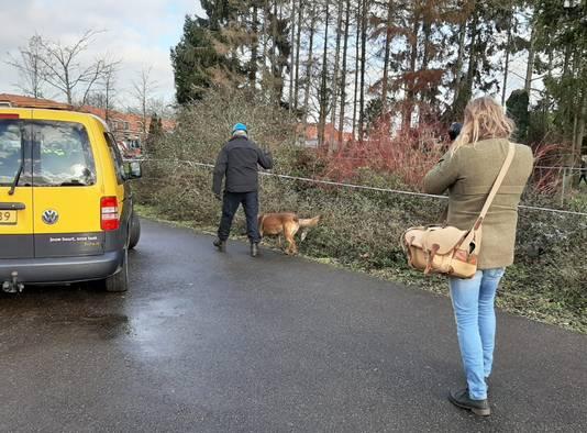 Een begeleider met speurhond zoekt naar sporen bij de uitgebrande woning aan de Nieuweweg in Doetinchem.