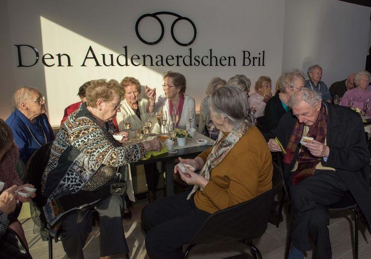 """De senioren genoten op de feestelijke opening met volle teugen van hapjes en drankjes in cafetaria """"Den Audenaerdschen Bril"""", een knipoog naar de geschiedenis van de stad."""