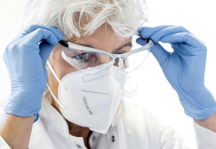 Een huisarts kleedt zich om in beschermende kleding om een patiënt met corona in de praktijk te ontvangen.