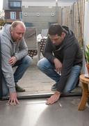 Bouwdeskundige Danny Veerman (r) voelt aan de ongelijke vloer van Ricardo Doeser.