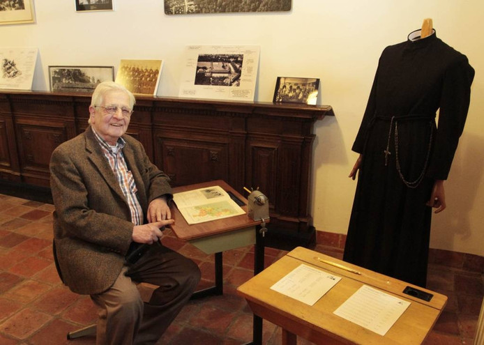 Broeder Adri Franken, conservator van het Wilhelmietenmuseum in Huijbergen, weer even in de schoolbanken met voor hem een aardrijkskundeboek uit 1928.
