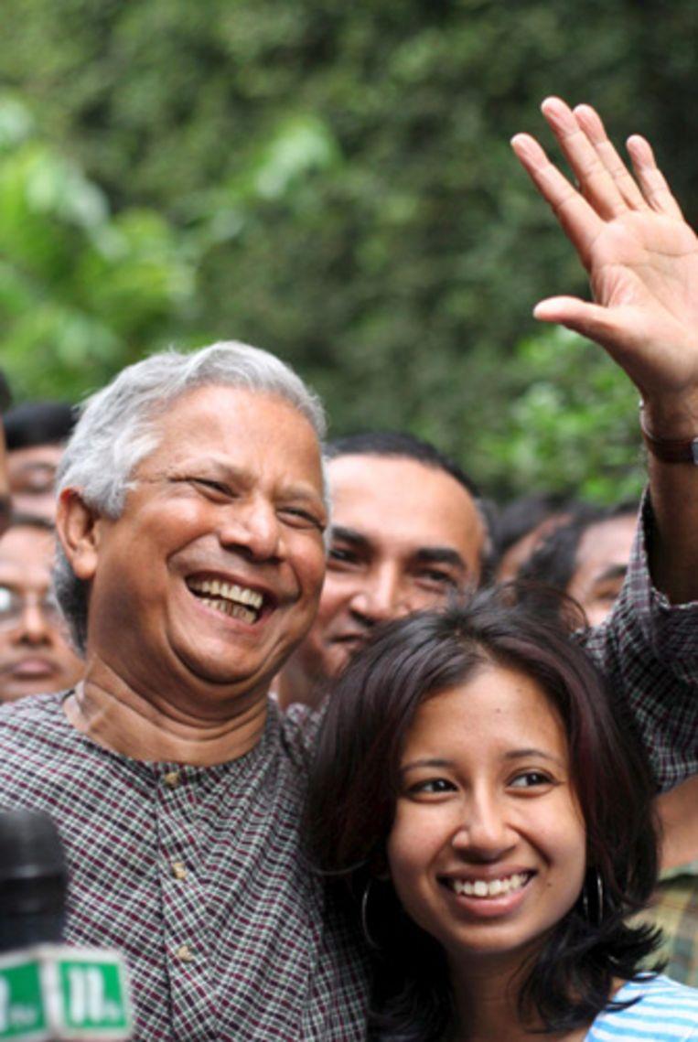Vredesnobelprijswinnaar Muhammad Yunus, hier omarmd door zijn dochter Dina, groet breed lachend en vol ongeloof over de gewonnen prijs zijn collega's bij de Grameen Bank. (AP) Beeld null