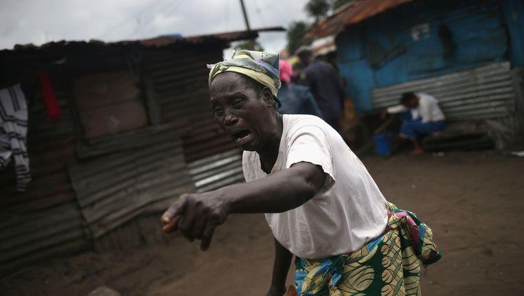 Een Liberiaanse vrouw huilt nadat het lichaam van de 28-jarige Mekie Nagbe, gestorven aan ebola, is weggedragen. Beeld getty