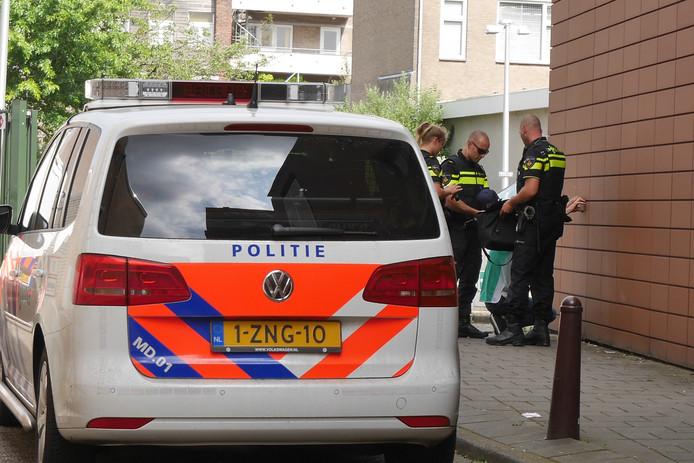 Politiemensen houden de arrestant in bedwang.