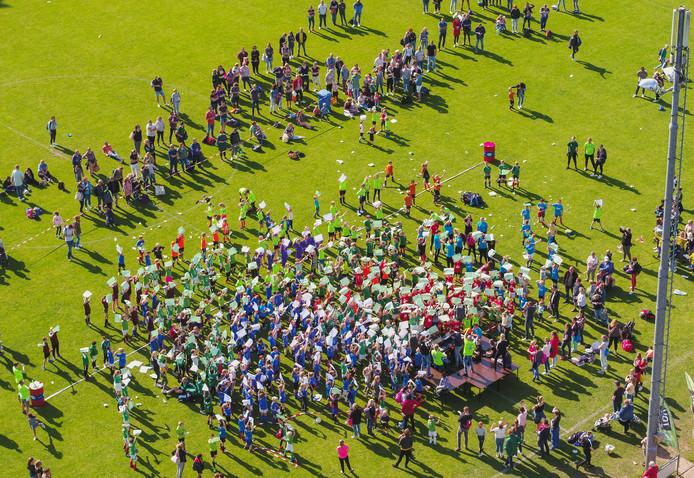 Na afloop van het mini-schoolvoetbaltoernooi verzamelen honderden leerlingen en ouders zich op hoofdveld van SVVN voor een soort flashmob op muziek. Met groene en witte A3-vellen worden patronen/figuren uitgebeeld.