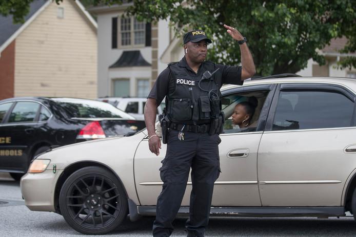 Een politieagent in DeKalb County in de Amerikaanse staat Georgia leidt het verkeer om nadat tien kinderen beschoten werden met een luchtgeweer.