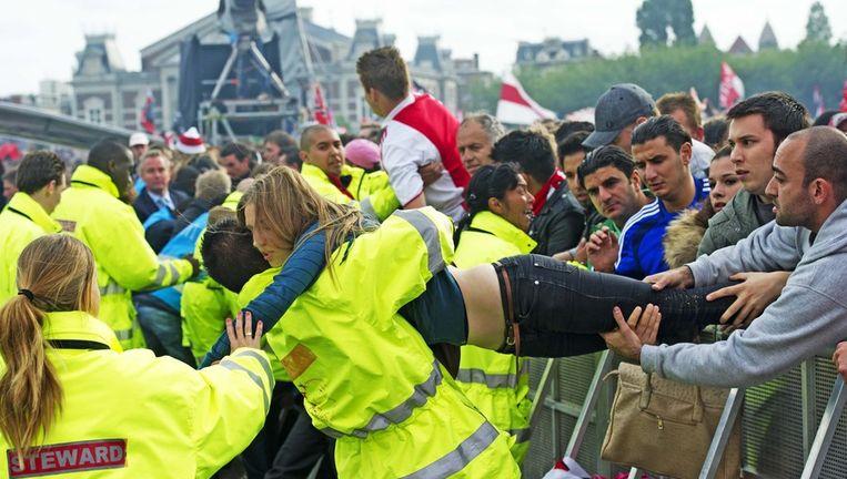 Een vrouw wordt door de hulpdiensten uit het publiek gehaald tijdens de huldiging van Ajax afgelopen zondag. Foto ANP Beeld