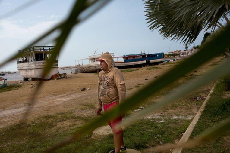 Enrique Torres kijkt toe hoe andere zeemannen kratten frisdrank  op de boten aan de kade van La Vela laden. Beeld Manaure Quintero