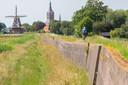 De niet meer in al te beste staat verkerende muur is als overblijfsel van de waterkering van de voormalige Zuiderzee een Rijksmonument
