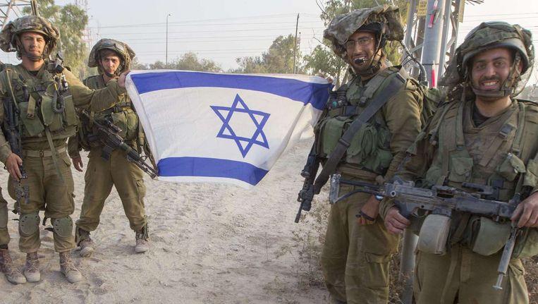 Israëlische soldaten poseren met de nationale vlag. Beeld afp