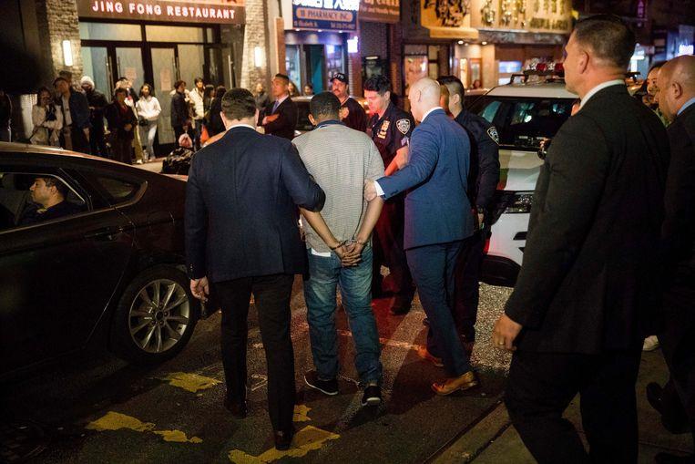 Verdachte Randy Rodriguez Santos wordt door agenten weggeleid.
