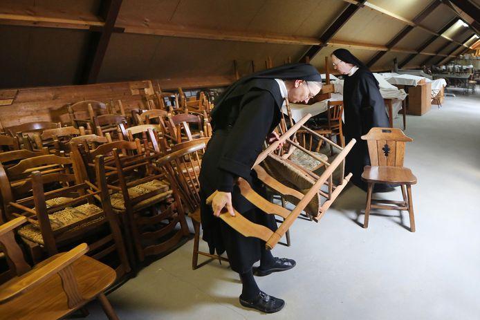 De benedictinessen van de Onze Lieve Vrouweabdij verkopen vanwege een grote verbouwing overtollige meubels en spullen. Zuster Simone van Brink (L) en Zuster Lydia Nijhuis (R) zoeken de stoelen uit op de zolder van het complex.