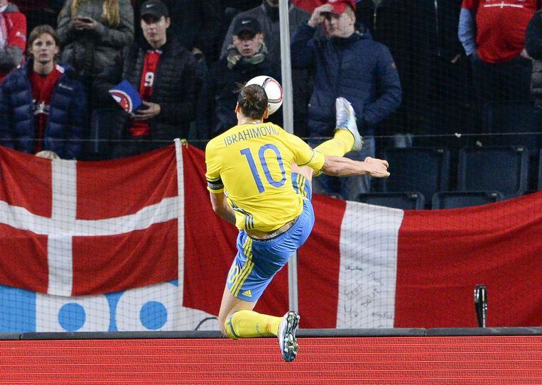 Deense supporters kijken toe hoe Ibrahimovic een bal uit de lucht opvangt. Beeld afp