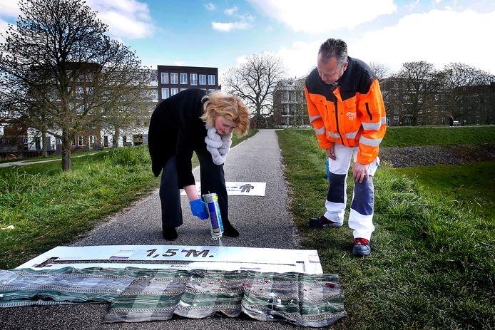 Burgemeester Reinie Melissant spuit verf in het sjabloon dat exact anderhalve meter afstand aangeeft. Henk Spoor van de gemeentelijke buitendienst kijkt of het goed gaat.