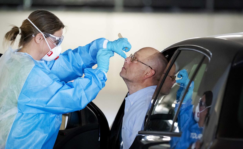 Vice-premier Hugo de Jonge roept iedereen op om zich al bij milde klachten op corona te laten testen. Dat kan bij de GGD in een drive-in teststraat, zoals op de foto.  Beeld ANP