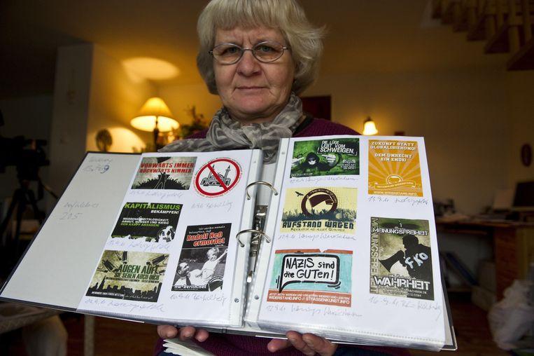 Irmela Mensah-Schramm toont een deel van haar collectie aan verwijderde nazi-stickers. Beeld AFP