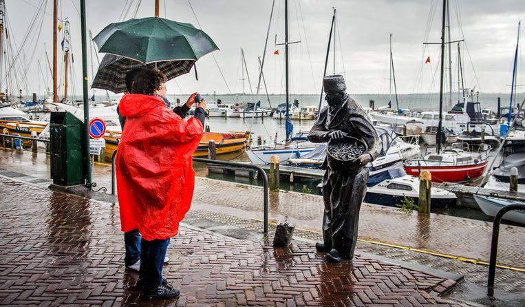 Toeristen met paraplu's trotseren de regen in de oude haven van Volendam. Beeld ANP