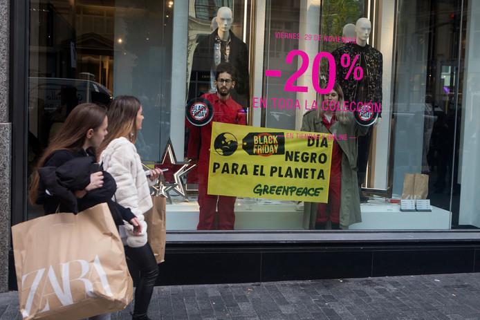 Shoppers in Madrid zien activisten van Greenpeace in een etalage. Hun boodschap: Black Friday is een zwarte dag voor de planeet.