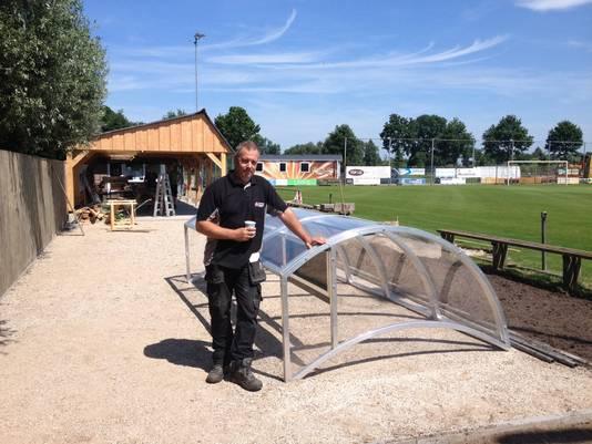 Aannemer Ron Menkhorst bij een deel van de nieuwe dug out van SV Westendorp. Die staat nu nog op de nieuwe jeu-de-boulesbaan. Op de achtergrond de uitbreiding van de overkapping.