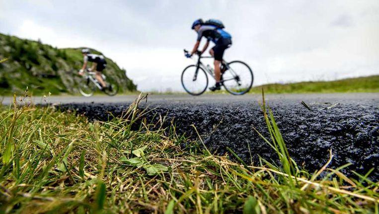 Wielrenners rijden op het nieuw asfalt in de afdaling van de Col de Sarrene, de rustige kant van de Alpe d'Huez, een dag voordat de renners van de Tour de France de berg beklimmen. Beeld anp