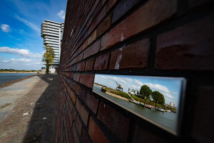 Aan de muur van de nieuwe verlaagde kade van de Waalhaven zijn spiegelstenen geschroefd.