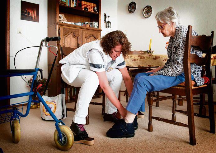 Een verpleegkundige helpt een van haar cliënten na het zwachtelen van de benen in aangepaste sloffen