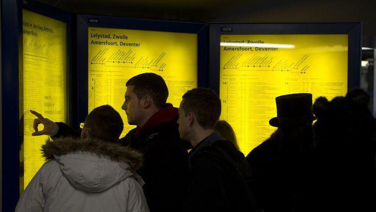 Treinreizigers bekijken op station Amsterdam Centraal de nieuwe dienstregeling van de Nederlandse Spoorwegen die is ingegaan. Beeld ANP