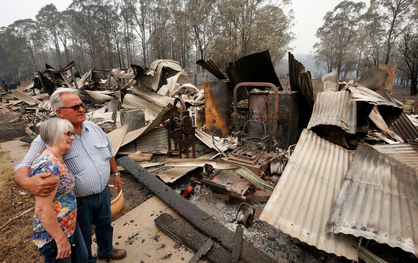 Lyn and Peter Iverson bekijken de resten van hun stal en kantoor in Koorainghat, New South Wales.
