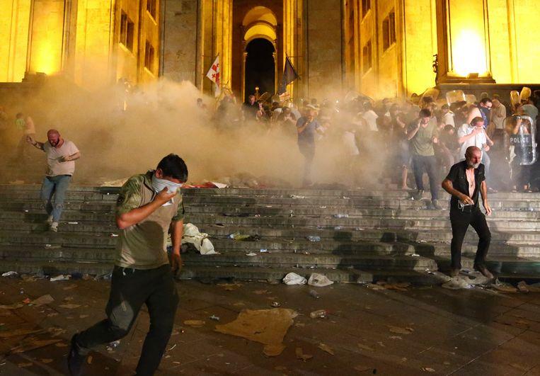 Demonstranten te midden van traangaswolken tijdens de gewelddadig verlopen protesten bij het Georgische parlement. Beeld AP