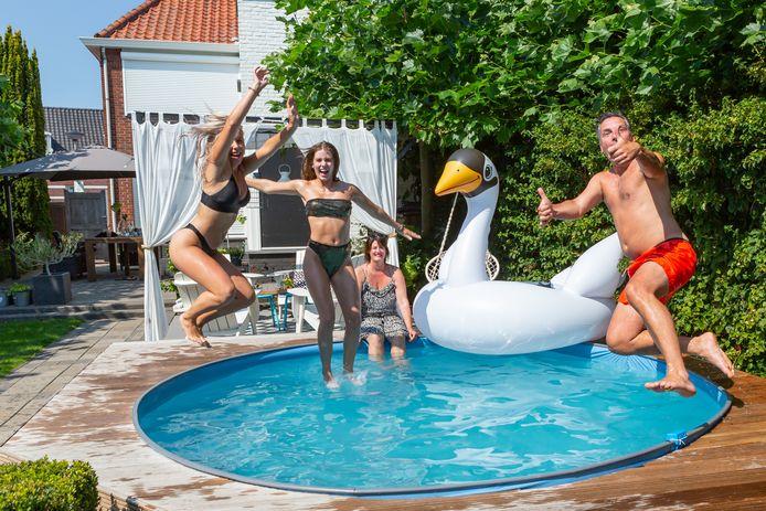 """Ibiza in de achtertuin. Het huishouden Buijs in Ossendrecht was uitgekeken op trampoline en heeft de grond wat verder uitgediept op die plek, om er te kunnen zwemmen. ,,De zon staat daar goed. En ik had de tijd omdat er geen voetbal was."""" Op de foto Moniqe, Britt en Arjan Buijs en Esther Goossens."""