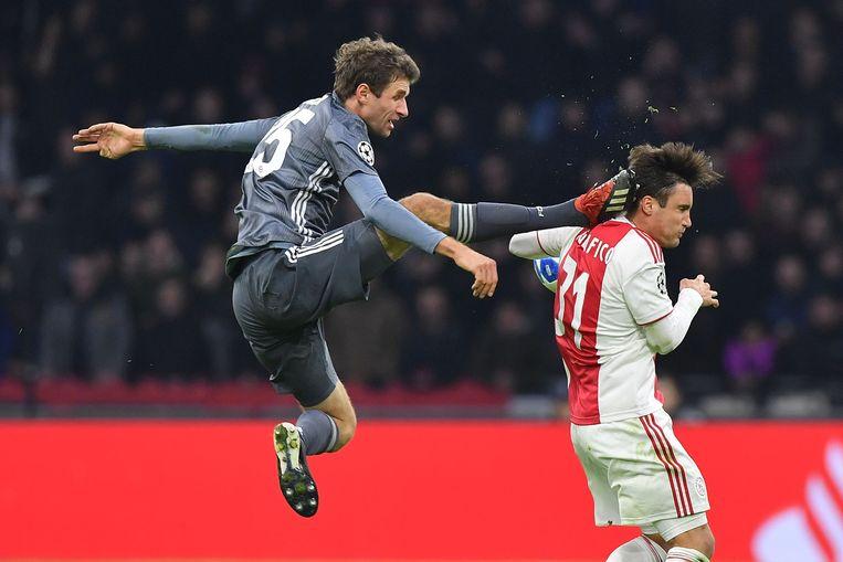 Nicolas Tagliafico wordt vol geraakt in de nek door Thomas Mullert, rood krijgt de Bayernspeler. Beeld AFP