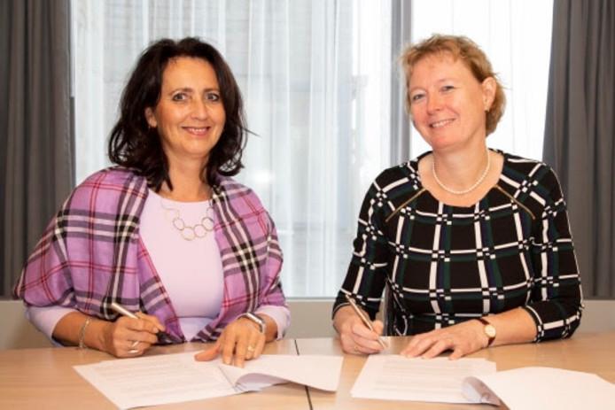 Paula Nelissen, bestuurder van Oktober (links) en Christianne Lennards, bestuurder van het MMC, tekenen de samenwerkingsovereenkomst.