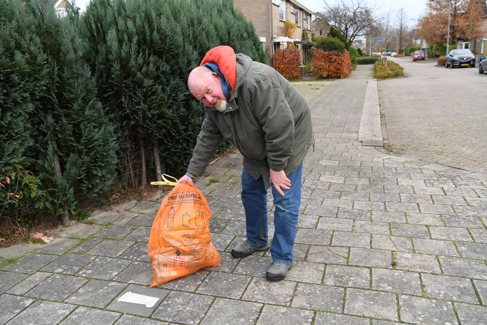 Oosterhouter Ivo Naninck toont een oranje zak die de gemeentelijke ophaaldienst niet heeft meegenomen.
