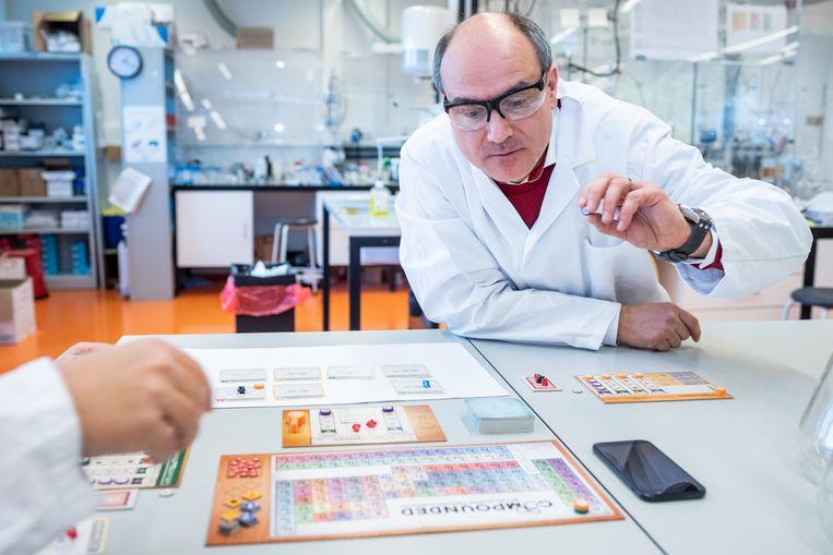 Chemicus Bert Weckhuysen buigt zich in zijn lab in Utrecht over bordspel Compounded. Op tafel ligt het periodiek systeem der elementen, waarop spelers hun score bijhouden. Beeld Simon Lenskens
