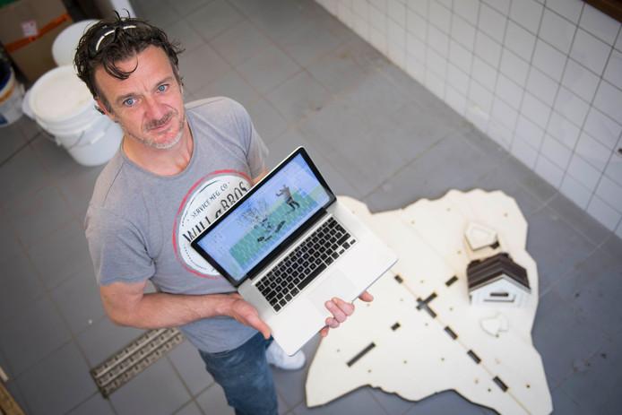 Frank Ulijn legt de laatste hand aan het kunstwerk dat zondag onthuld wordt. Op zijn laptop het ontwerp.