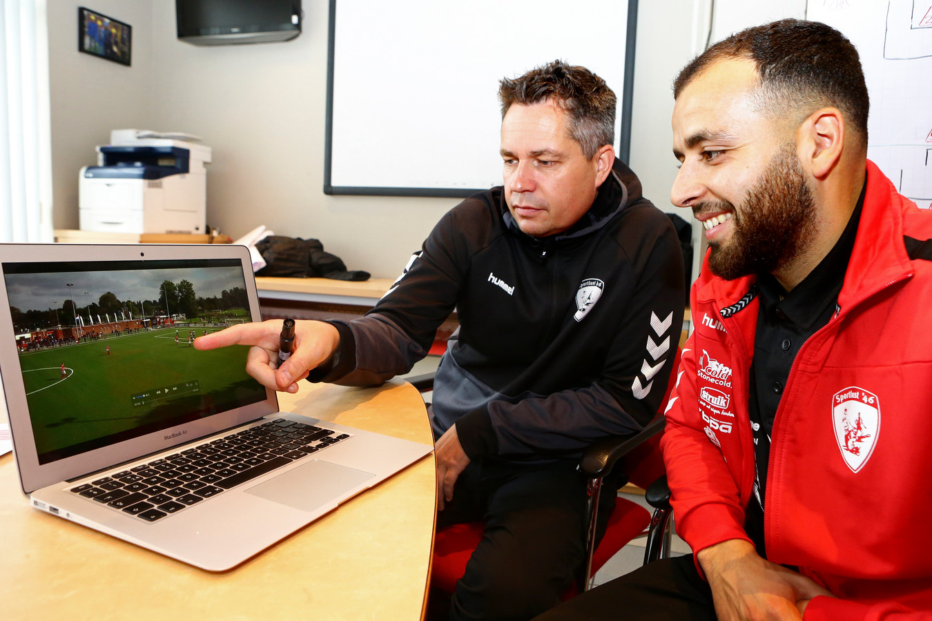 Trainer Patrick Loenen van Sportlust 46 bespreekt de wedstrijd met speler Abdoel aan de hand van televisiebeelden.