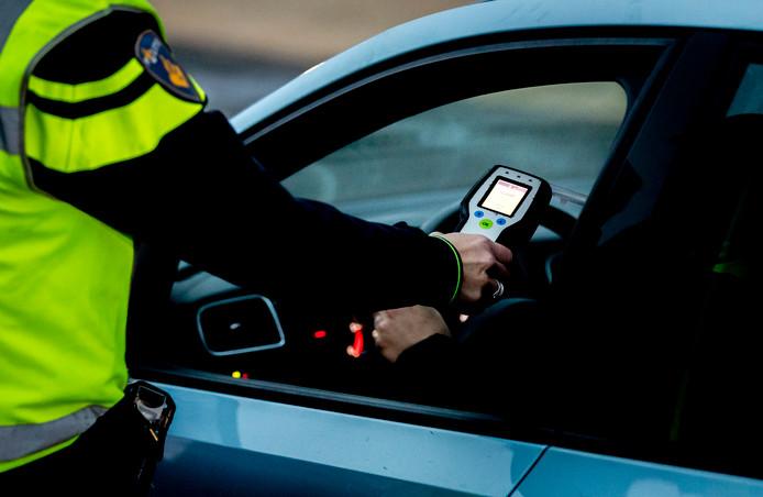 Archiefbeeld: Een politieagent voert een alcoholcontrole uit tijdens een verkeerscontrole.