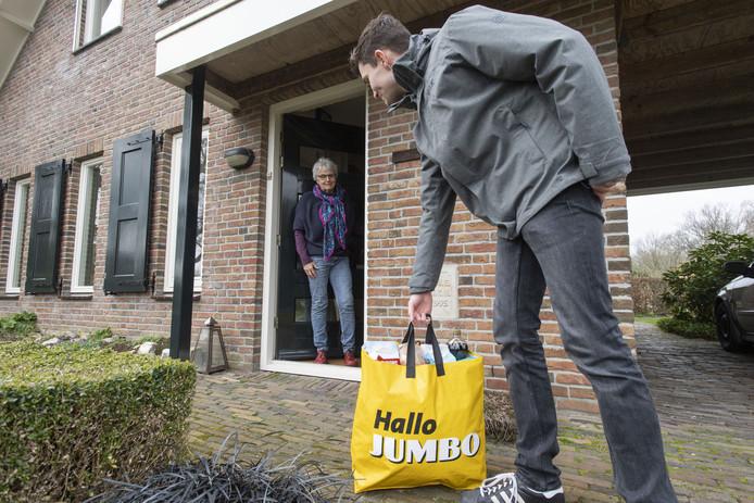 Boodschappen worden bij ouderen bezorgd. Er is geen contact, de boodschappentas wordt bij de deur neergezet, waarna de bezorger afstand neemt.