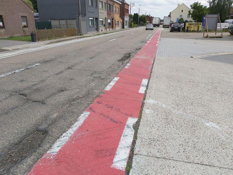 Het fietspad en de weg in slechte staat aan de uitrit van de AB InBev brouwerij