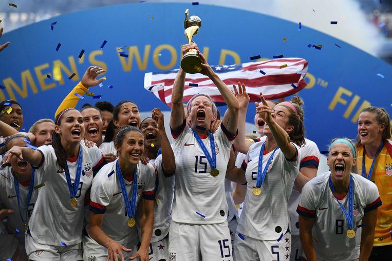 Megan Rapinoe in het midden samen met de rest van haar team, trots met de trofee in haar handen. Beeld AFP