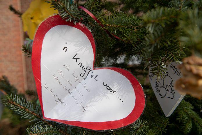 Bemoedigingsbomen bij de St. Antonius van Padua kerk hangen vol kaartjes en slingers.  Jos van den Berg bij de boom.