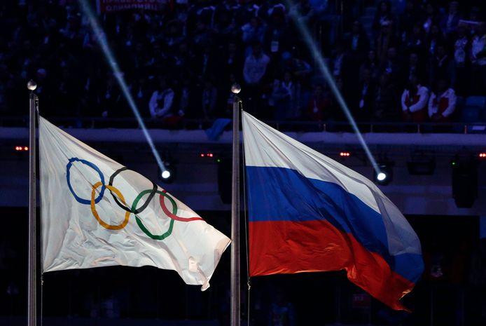 De Russische en de olymische vlag wapperen naast elkaar tijdens de slotceremonie van de Winterspelen in Sotsji in 2014.