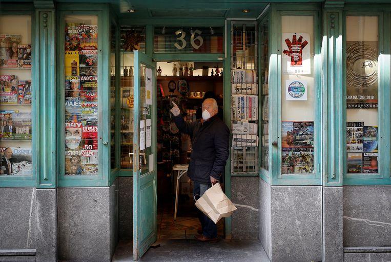 Een man draagt een mondmasker en handschoenen om een krant te kopen in Pamplona. Beeld EPA