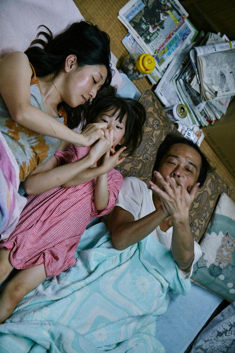 Vader en moeder in Shoplifters, met de geadopteerde, hartveroverende Yuri in hun midden.  Beeld eenmalig K2 - filmbeeld