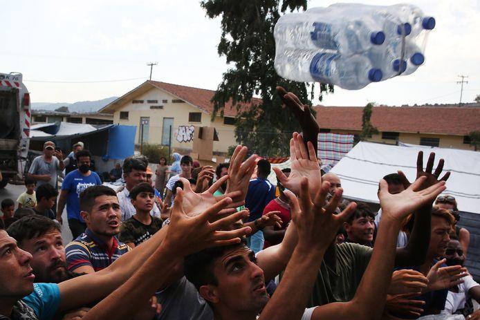 Vluchtelingen komen bijeen voor wat water en voedsel dat door hulporganisaties wordt verdeeld.