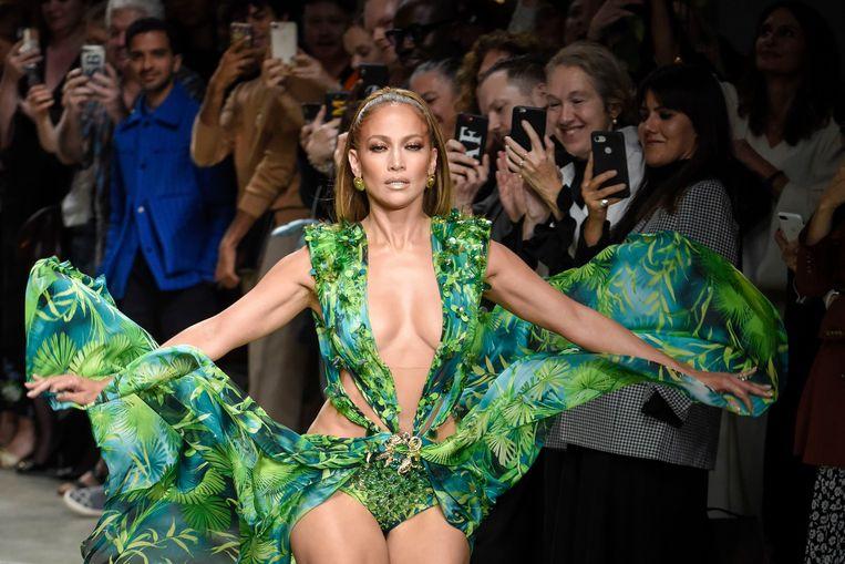 Jennifer Lopez op de Versace-show tijdens de Milaan Fashion Week 2019 waar ze een vernieuwde versie van de iconische jurk uit 2000 draagt die gekopieerd werd door Fashion Nova.