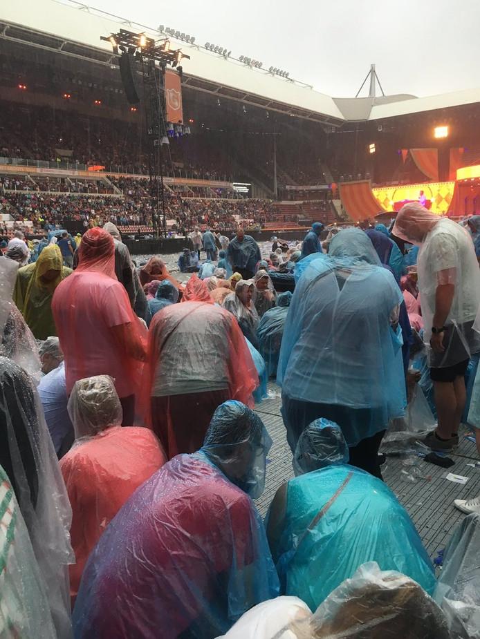 Publiek zit gehurkt op het veld van het Philips Stadion.