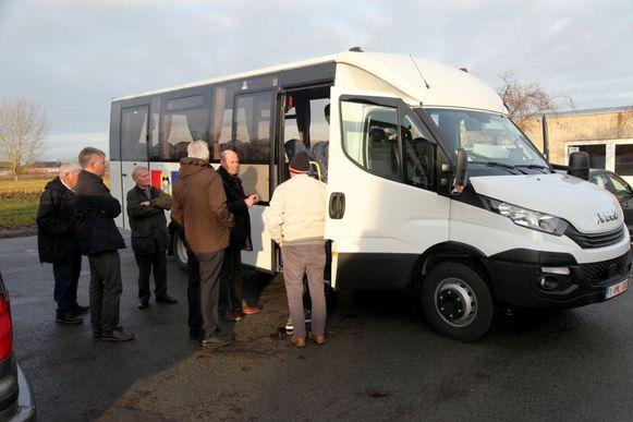 De directeur inspecteert de bus samen met de makers van de schoolbus, de chauffeurs en een lid van het schoolbestuur.